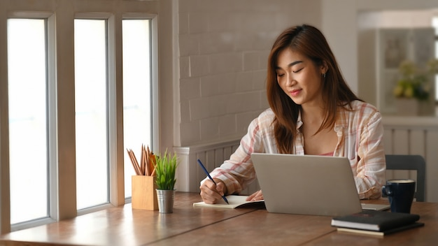Beautiful woman writing/taking notes while sitting in front her computer laptop at the wooden working table over living room bookshelf