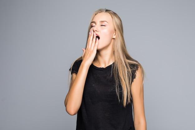 Красивая женщина зевает, скучно, изолированные на сером фоне