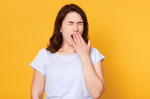 Beautiful woman yawns isolated over yellow