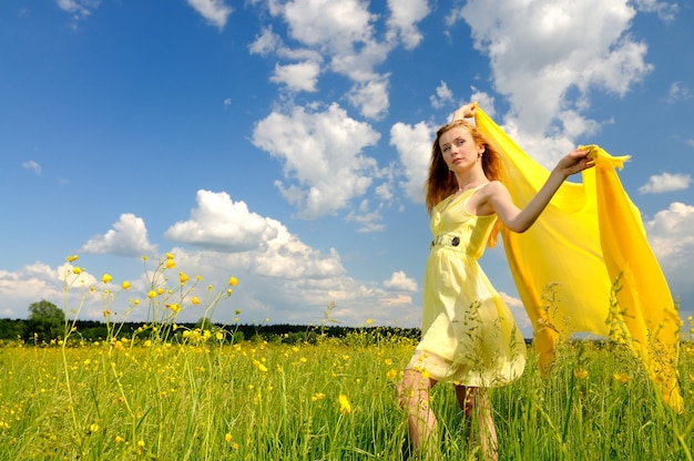 Beautiful woman in a yellow cocktail dress posing in a green field with airiness silk in her hands