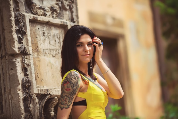 A beautiful woman in a yellow dress, tattoos, posing for photos architecture in lviv