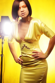 Beautiful woman  in yellow dress on yellow background