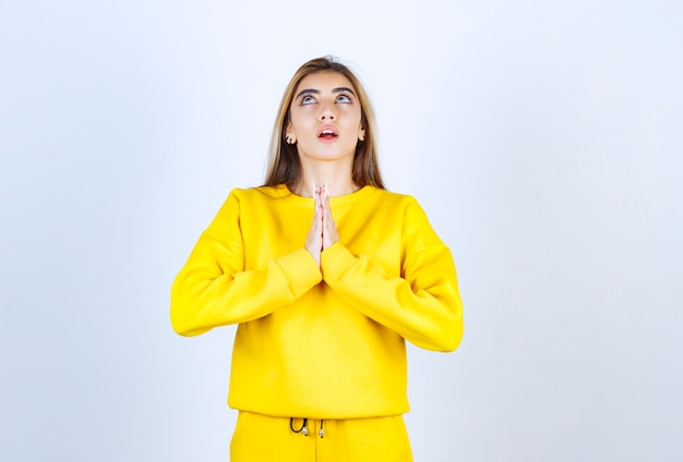 Beautiful woman in yellow sweatsuit standing and praying over white wall