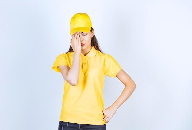 Bella donna in maglietta gialla e berretto che si sente depressa su sfondo bianco.