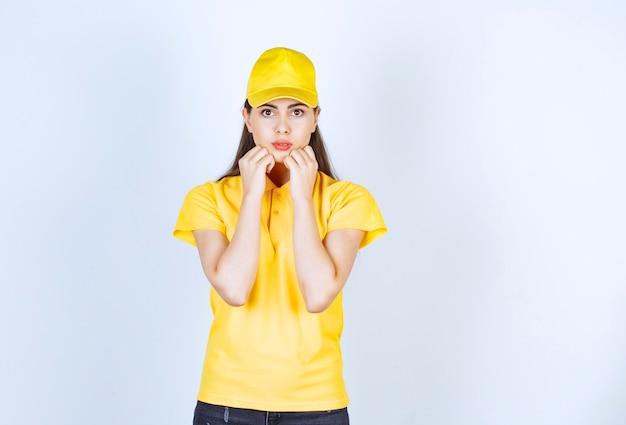 Bella donna in maglietta gialla e berretto scioccata per qualcosa su sfondo bianco.