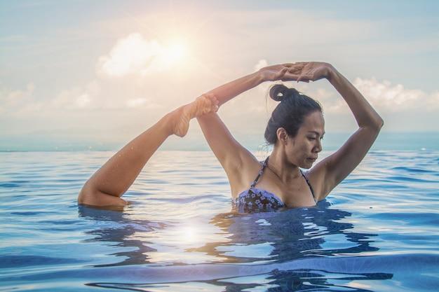 Beautiful woman yoga in turquoise blue swimming pool.