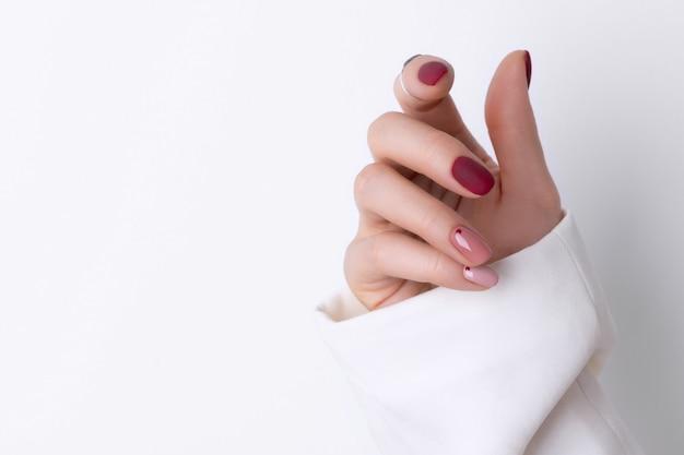 最小限のスタイルでピンクのマニキュアで美しい女性の手