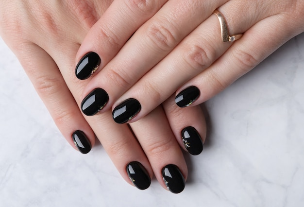 Beautiful womans hand with elegant manicure on marble background. minimal black nail design.