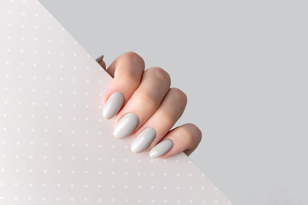 Beautiful womans hand with manicure close up on polka dot background. gray nail polish