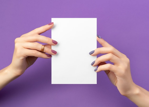Beautiful womans hand with manicure holding postcard on purple