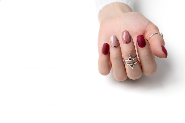 Beautiful womans hand with a pink manicure in minimal style