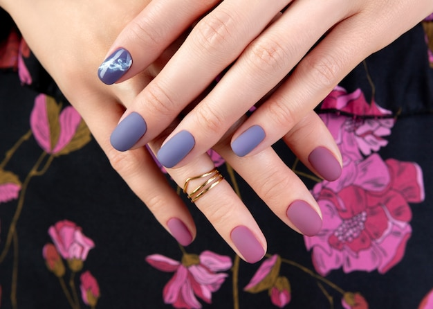 Beautiful womans hand with purple matte manicure on fabric