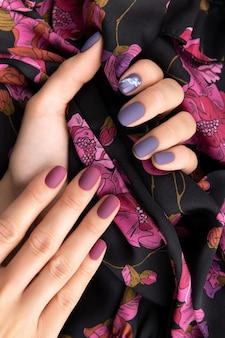 生地を保持している紫のマット マニキュアで美しい梨花の手