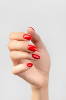 グレーに赤いマニキュアで美しい女性の手