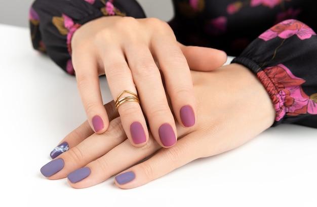 紫色のバーガンディ マット マニキュアで美しい女性の手