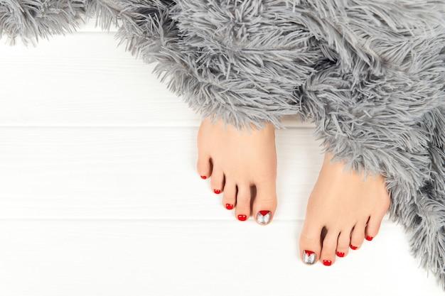 Красивые женские ноги с пушистым одеялом на деревянном фоне