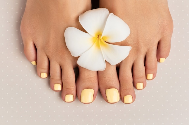 회색 폴카 도트 표면에 여름 네일 디자인으로 아름다운 여자 다리