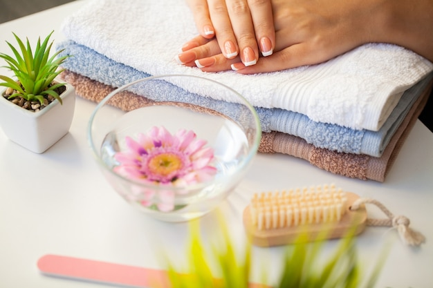 Beautiful womans nails with french manicure in beauty studio
