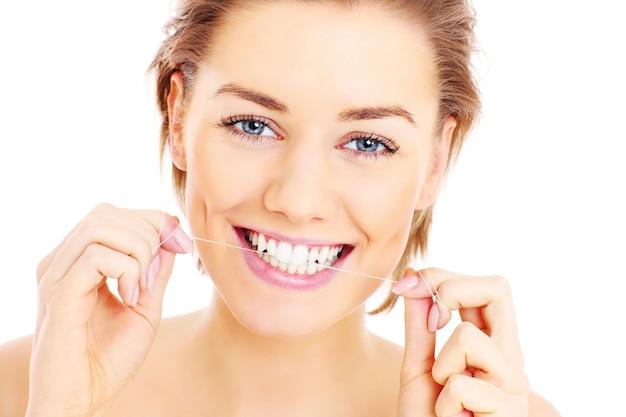 白い背景の上に彼女の歯にデンタルフロスを使用して美しい女性