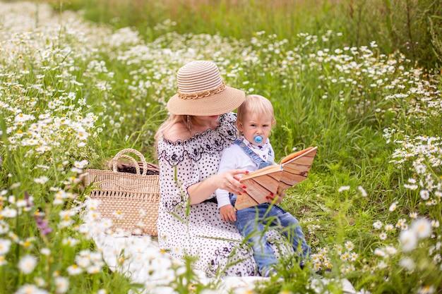 美しい女性と彼女の息子が座って本を読んでいます。高品質の写真