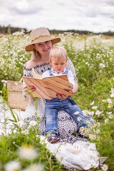 Красивые женщины и ее сын сидят и читают книгу. фото высокого качества