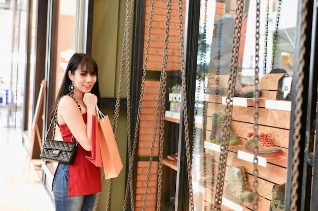 아름다운 여성은 쇼핑몰에서 쇼핑을 기쁘게 생각합니다