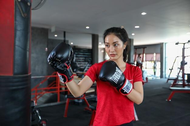 美しい女性アジアのボクサー幸せで楽しいフィットネスボクシングとボクシンググローブを着用してバッグをパンチ。