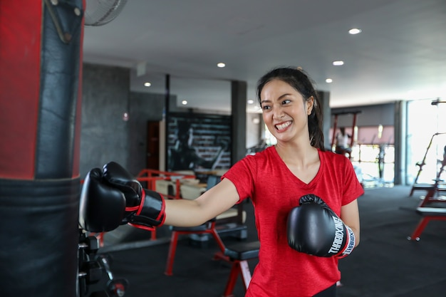 Beautiful women asian boxer happy and fun fitness boxing and punching a bag with wearing boxing gloves.