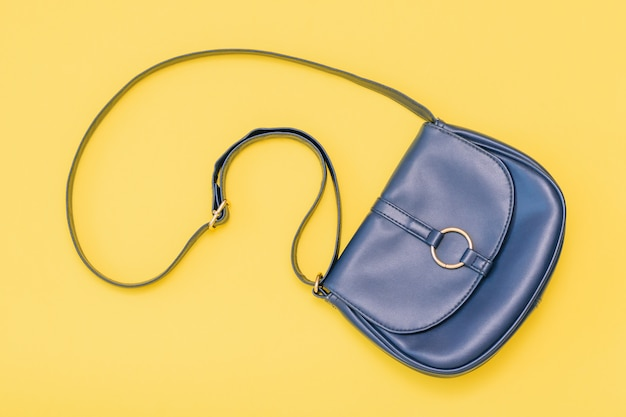 Beautiful women bag of blue leather on yellow background. the view from the top. flat lay.