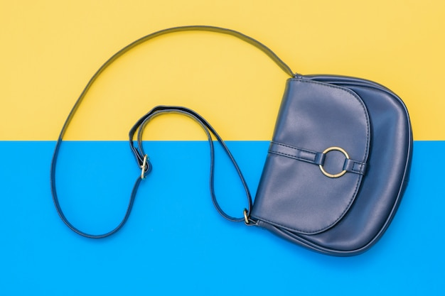 Beautiful women bag of blue leather on yellow and blue background. the view from the top. flat lay.