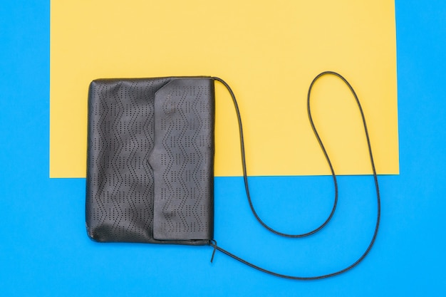 Beautiful women black bag of blue leather on yellow and blue background. the view from the top. flat lay.