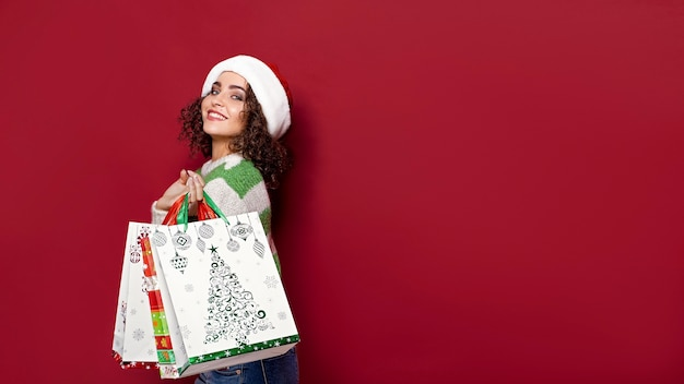 Beautiful women carrying bright christmas colorful shopping bags on red background. christmas shopping and happy new year.