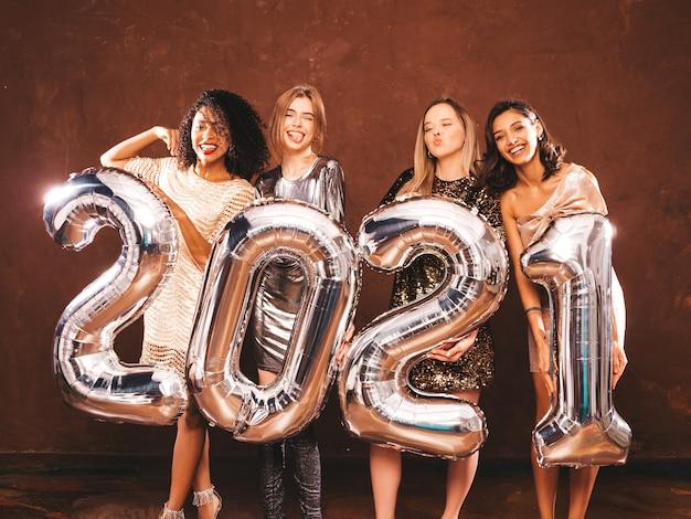 새해를 축하하는 아름다운 여성. 세련된 섹시한 파티 드레스를 입고 은색 2021 풍선을 들고 새해 전야 파티에서 즐거운 시간을 보내는 아름다운 여성. 휴일 축하