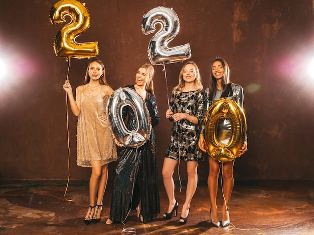 Beautiful women celebrating new year. happy gorgeous girls in stylish sexy party dresses holding gold and silver 2020 balloons, having fun at new year's eve party. holiday celebration.charming models