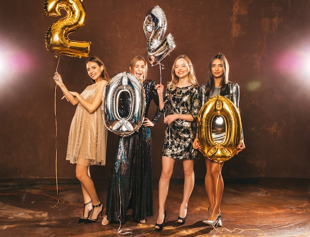 Beautiful women celebrating new year. happy gorgeous girls in stylish sexy party dresses holding gold and silver 2020 balloons, having fun at new year's eve party. holiday celebration.raising hands