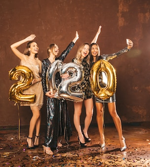 Beautiful women celebrating new year.happy gorgeous girls in stylish sexy party dresses holding gold and silver 2020 balloons, having fun at new year's eve party.making selfie or video for instagram