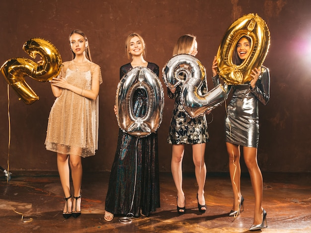 Beautiful women celebrating new year.happy gorgeous girls in stylish sexy party dresses holding gold and silver 2020 balloons, having fun at new year's eve party.