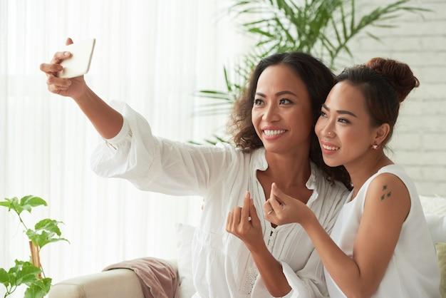 自宅でスマートフォンで自分撮りをするときに指ハートをしている美しい女性
