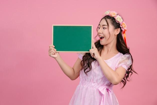 ピンクプリンセスドレスに身を包んだ美しい女性は、ピンクの緑のボードを保持します。