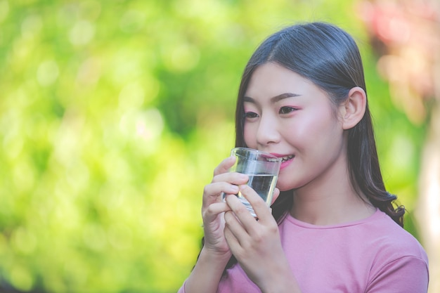 Beautiful women drink clean water from a glass of water