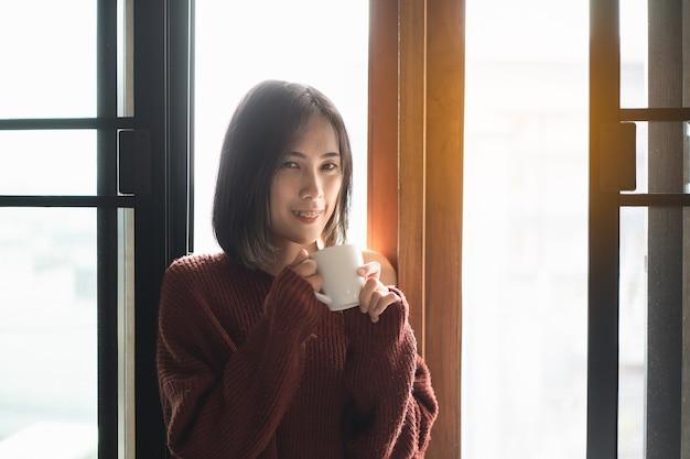 寝室の窓の横でホットコーヒーを飲む美しい女性