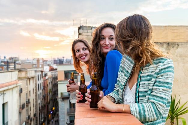 Beautiful women enjoying a beer on a rooftop in barcelona