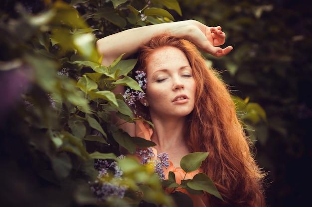 緑豊かな公園の花とライラックガーデン、若い女性を楽しむ美しい女性。屋外を歩く陽気な10代の若者。柔らかな光スタイルの色