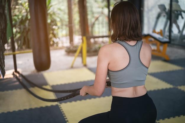 美しい女性がジムでバトリンロープを使ってトレーニングを行う、スポーツフィットネスのコンセプト