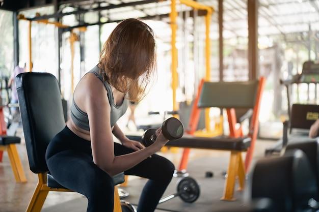 아름다운 여성은 체육관에서 아령 훈련, 스포츠 피트니스 개념 운동