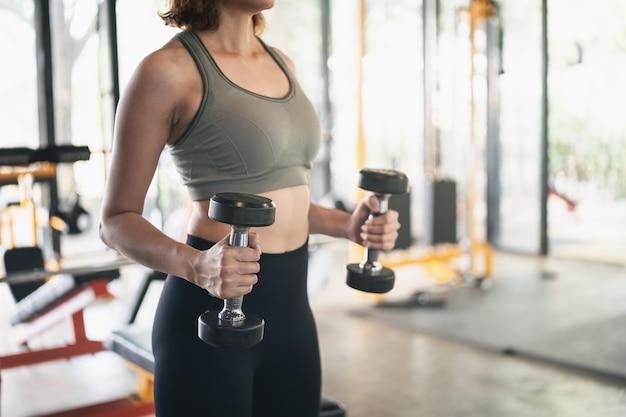 美しい女性がジムでダンベル、スポーツフィットネスの概念でトレーニングを行使する