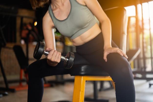 美しい女性がジムでダンベル、スポーツフィットネスのコンセプトでトレーニングを行使