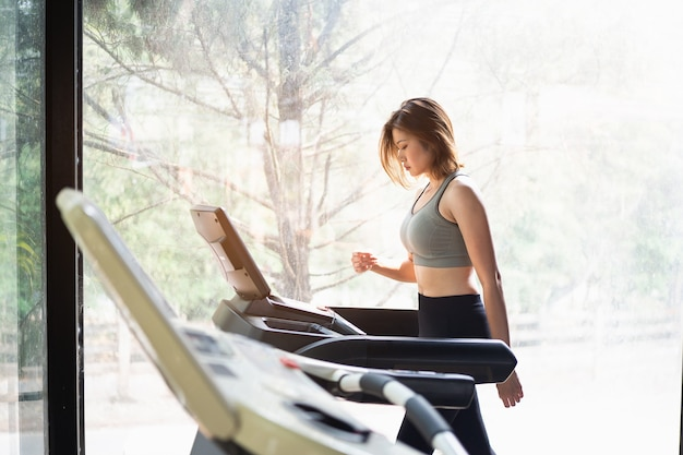 Beautiful women exercise training with treadmill in the gym, sport fitness concept