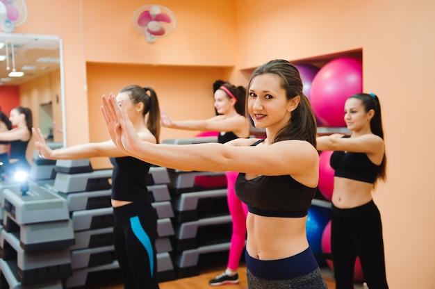 Beautiful women exercising aerobics in fitness club