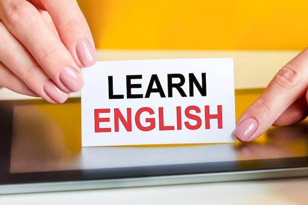 美しい女性の手は、テキストで白い紙を持っています:英語を学ぶ